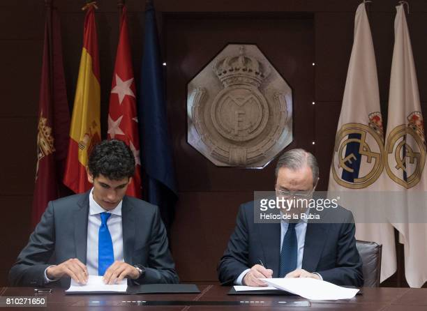 Jesus Vallejo of Real Madrid signs his contract beside Real Madrid president Florentino Perez during his official presentation at Estadio Santiago...