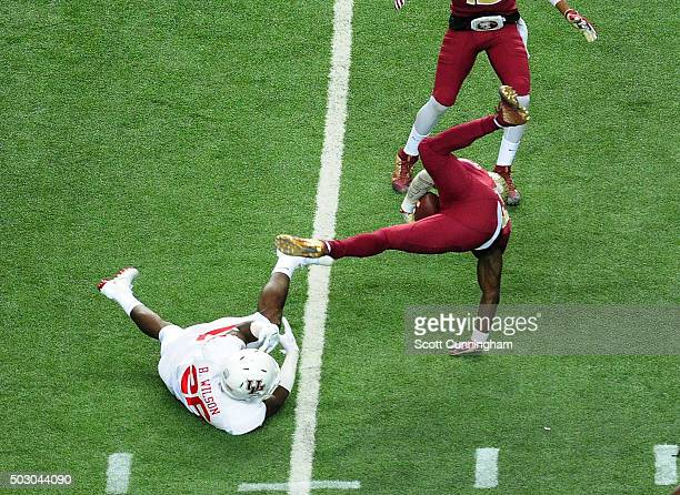 Jesus Wilson of the Florida State Seminoles is upended by Brandon Wilson of the Houston Cougars during the ChickFilA Peach Bowl at the Georgia Dome...