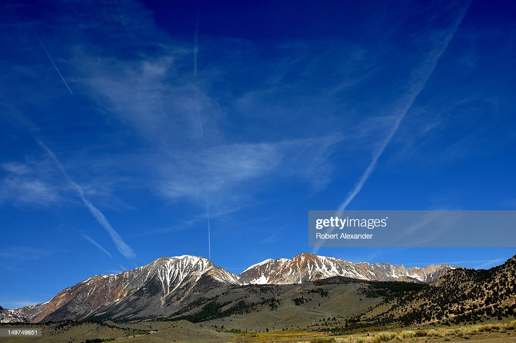 Jet aircraft contrails streak the sky above the Sierra Nevada mountain range near Lee Vining, California. (Photo by Robert Alexander/Archive Photos/Getty Images) 5104602RA_Sierra23.jpg