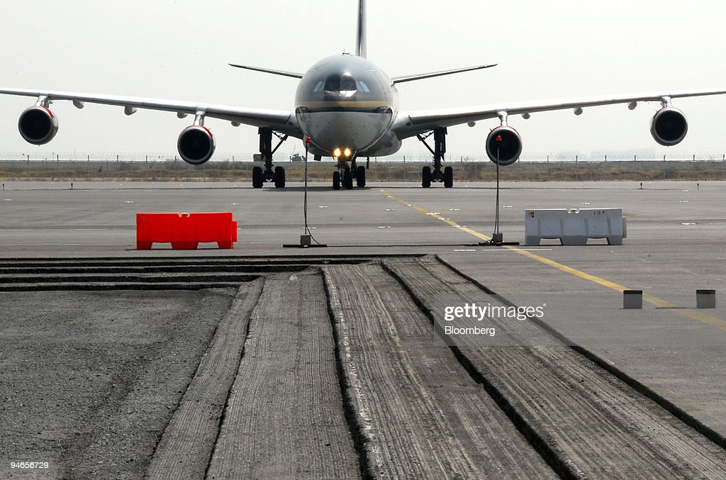 A jet airplane approaches an area where several layers of asphalt has been excavated on the apron of Bangkok's new Suvarnabhumi Airport during a...