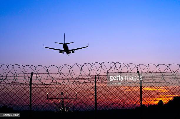 Jet airplane in the distance landing at sunset behind fence