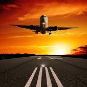 XL jet airplane landing at sunset