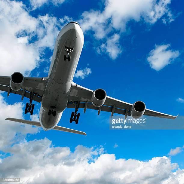 jet airplane landing in bright sky