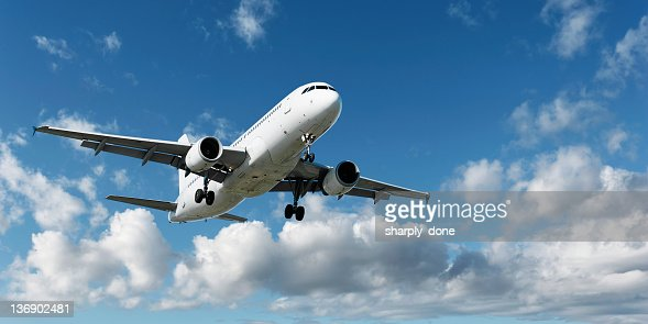 XL jet airplane landing in bright sky
