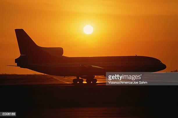 Jet airplane on tarmac at sunset