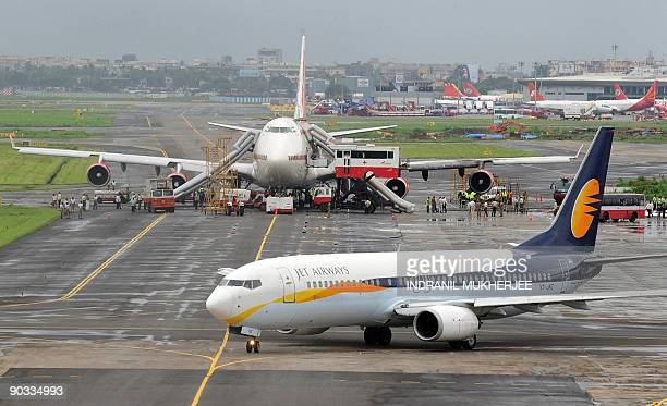 A Jet Airways aircraft prepares for takeoff as ground staff and emergency personnel of the fire brigade and disaster management teams surround the...