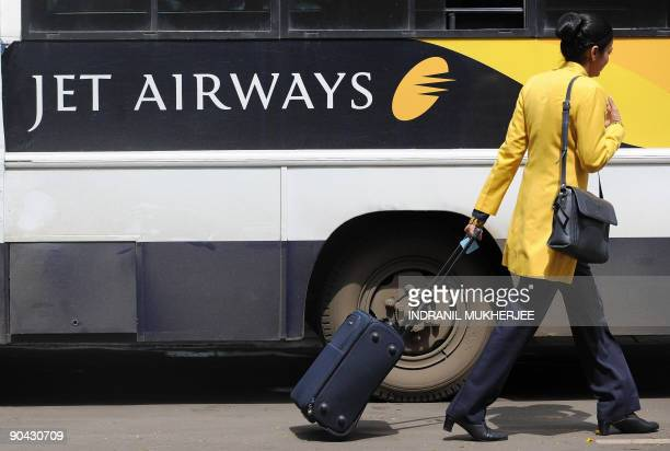 A Jet Airways flight attendant walks past a company coach at the city airport in Mumbai on September 8 2009 Flights on India's secondlargest private...