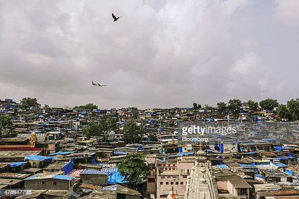 A Jet Airways India Ltd aircraft flies over slum housing as it approaches to land at Chhatrapati Shivaji International Airport in Mumbai India on...