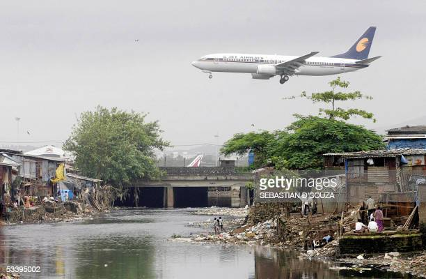 Jet Airways plane flies over the filthy Mithi River flanked on either side by slums on its way to landing at Mumbai airport at Bharat Nagar 16 August...