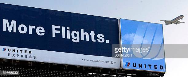 A jet descends into O'Hare International Airport in Chicago IL 06 December 2002 past a United Airlines billboard from when the airline was in a...