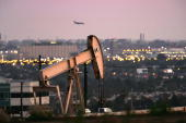 A jet lands at Los Angeles International Airport as oil rigs extract petroleum as the price of crude oil rises to nearly $120 per barrel prompting...