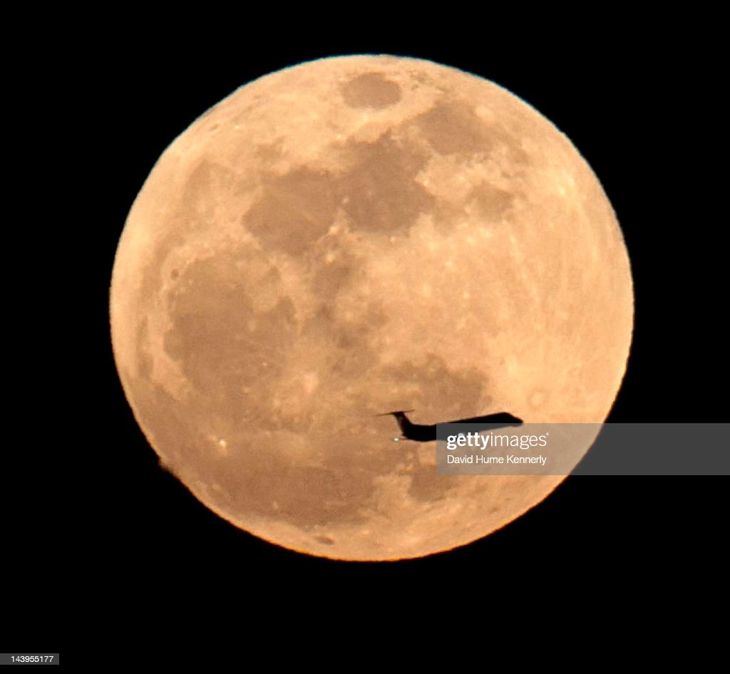 A jet on the approach to Los Angeles International Airport crosses in front of the 'Super Moon,' an event that occurs when the full moon reaches the part of its path that is closest to Earth seen from Baldwin Hills May 5, 2012 in Los Angeles, California. The moon appears especially big and bright during this once-a-year cosmic event as the full moon is at its closest to the Earth in its elliptical orbit. The perigee side of its orbit is about 31,000 miles closer than the opposite, or apogee, side. The bright light of the full moon also hides all but the brightest meteors of the Eta Aquarid meteor shower, the remnant debris trail of Halley's Comet. (Photo by David Hume Kennerly/Getty Images