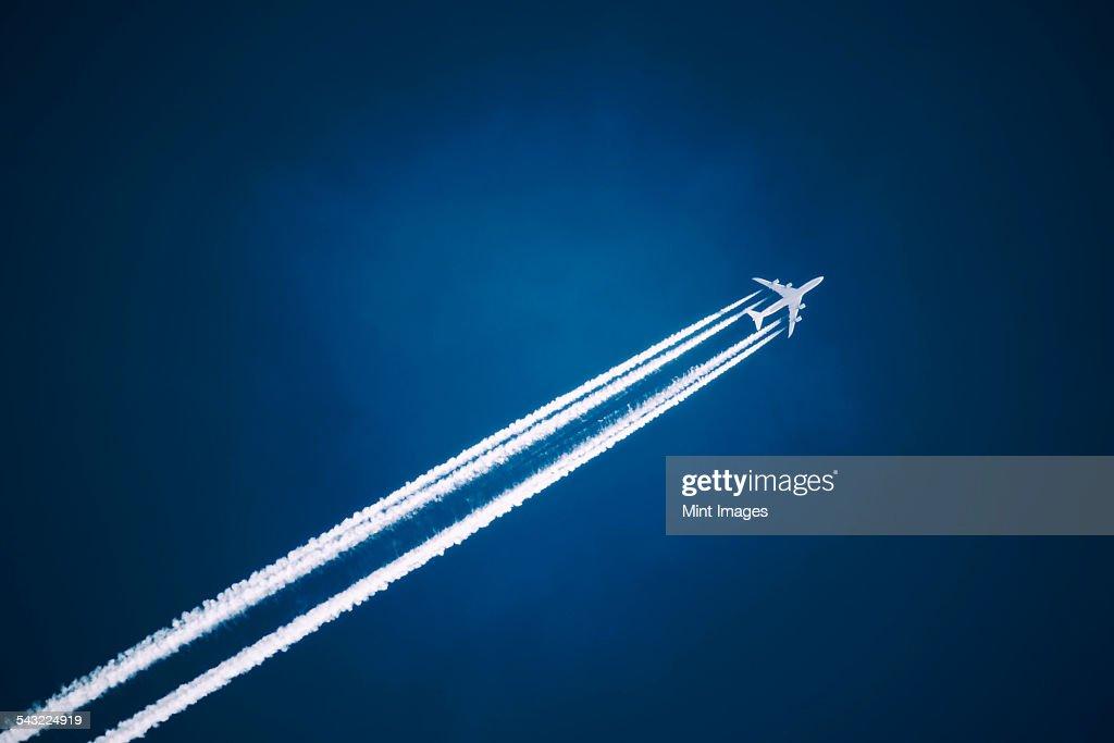 A jet vapour trail across a dark blue sky.