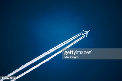 A jet vapour trail across a dark blue sky.