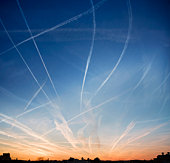 Jet vapour trails at sunset over rooftops
