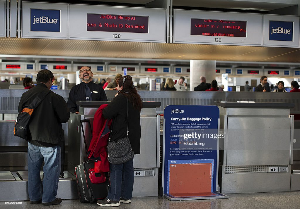 JetBlue Airways Corp. crew member Larry Osterkamp shares a laugh with customers as they check-in at San Francisco International Airport in San Francisco, California, U.S., on Monday, Jan. 28, 2013. JetBlue Airways Corp. fell the most in about two months after fourth-quarter profit tumbled 96 percent, more than analysts projected, as superstorm Sandy forced flight cancellations and reduced travel demand. Photographer: David Paul Morris/Bloomberg via Getty Images