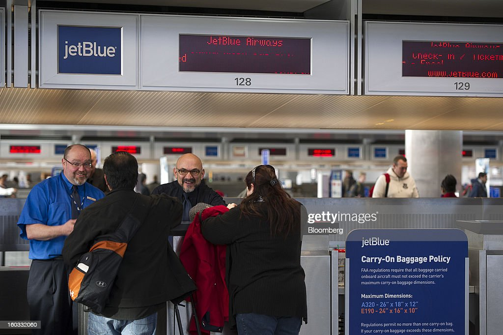 JetBlue Airways Corp. crew members Bill Sanderson, left, and Larry Osterkamp share a laugh with customers as they check-in at San Francisco International Airport in San Francisco, California, U.S., on Monday, Jan. 28, 2013. JetBlue Airways Corp. fell the most in about two months after fourth-quarter profit tumbled 96 percent, more than analysts projected, as superstorm Sandy forced flight cancellations and reduced travel demand. Photographer: David Paul Morris/Bloomberg via Getty Images