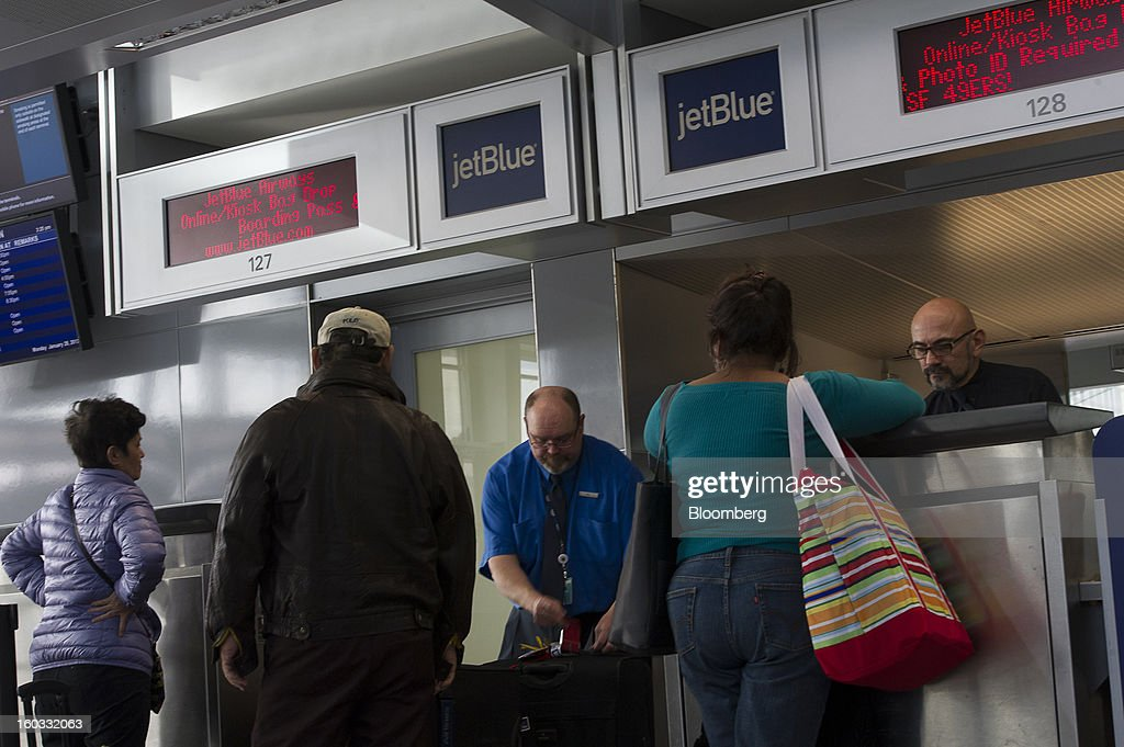 JetBlue Airways Corp. crew members Bill Sanderson, left, and Larry Osterkamp check-in customers at San Francisco International Airport in San Francisco, California, U.S.,, on Monday, Jan. 28, 2013. JetBlue Airways Corp. fell the most in about two months after fourth-quarter profit tumbled 96 percent, more than analysts projected, as superstorm Sandy forced flight cancellations and reduced travel demand. Photographer: David Paul Morris/Bloomberg via Getty Images