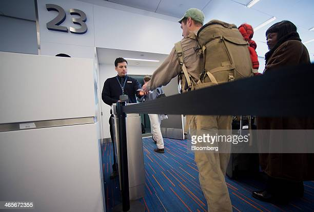 A JetBlue Airways Corp employee scans passengers tickets to board a flight at John F Kennedy International Airport in New York US on Tuesday Jan 28...