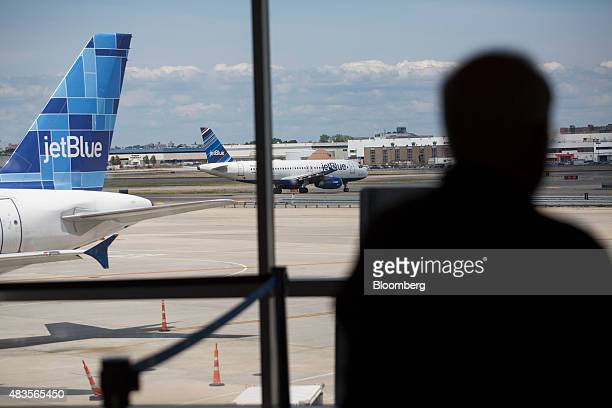 A JetBlue Airways Corp plane moves on the tarmac as a passenger waits in Terminal 5 at John F Kennedy International Airport airport in New York US on...