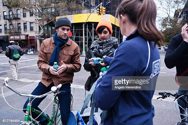 A JetBlue employee hands out free water to two young Manhattan residents outside of Tompkins Square Park The NYC Food Truck Assosciation in...
