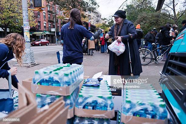 A JetBlue employee hands water to an older woman outside of Tompkins Square Park in Manhattan The NYC Food Truck Assosciation in collaboration with...