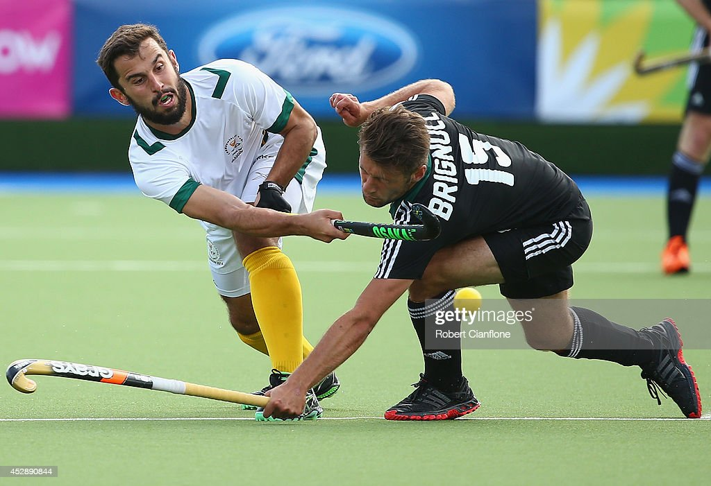 Jethro Eustice of South Africa is challenged by Liam Brignull of Wales during the men's preliminaries match between Wales and South Africa at the Glasgow National Hockey Centre during day six of the Glasgow 2014 Commonwealth Games on July 29, 2014 in Glasgow, United Kingdom.