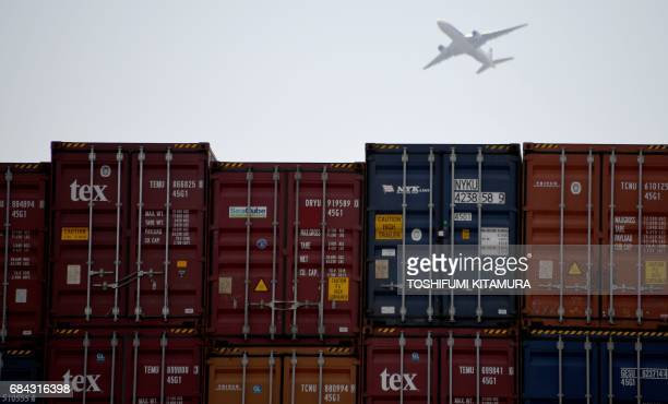 A jetliner flies over Oi container yard of the Tokyo port in Tokyo on May 18 2017 Japan has posted its longest economic expansion in over a decade...