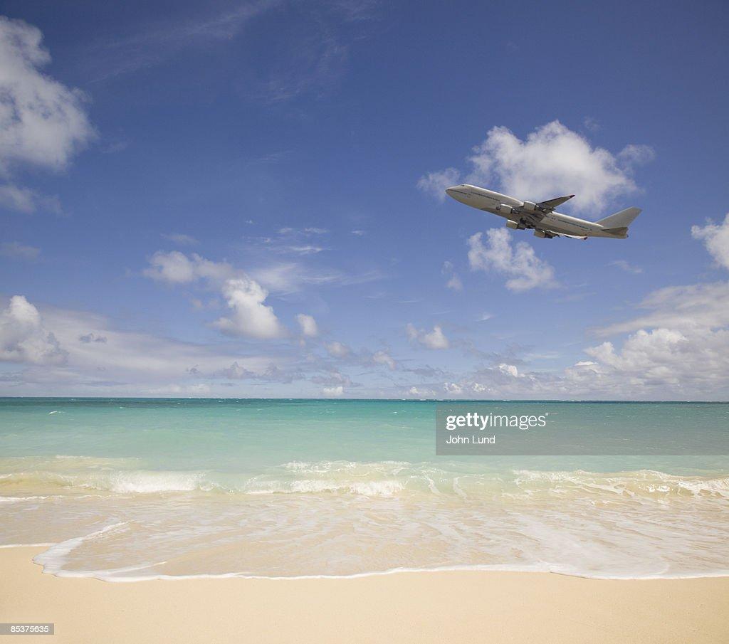 Jetliner flying over the beach : Stock Photo