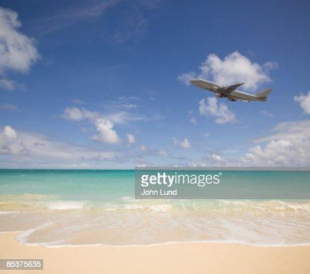 Jetliner flying over the beach : Bildbanksbilder