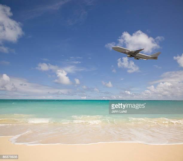 Jetliner flying over the beach