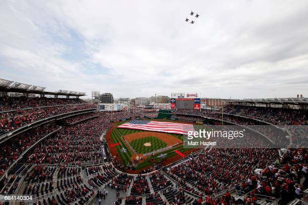 Jets fly over the stadium as the Miami Marlins and Washington Nationals line the field during the national anthem prior to the opening day game at...