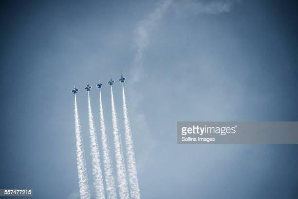 Jets flying in formation in cloudy blue sky