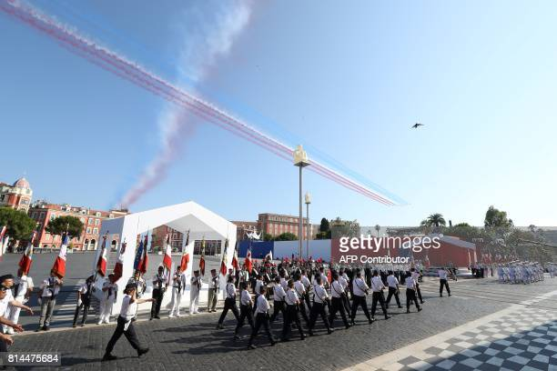 Jets of the Patrouille Acrobatique de France perform as members of the French Air Force parade during a commemorative ceremony marking the first...