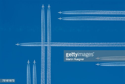 Jets with vapour trails in blue sky, view from below (digital composite)