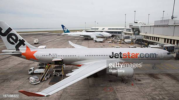 A Jetstar Airways aircraft foreground and an Air New Zealand Ltd aircraft stand on the tarmac at Auckland International Airport in Auckland New...