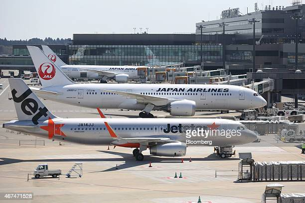 A Jetstar Japan Co aircraft front sits parked at Terminal 3 while Japan Airlines Corp aircrafts sit parked at Terminal 2 of Narita Airport in Narita...