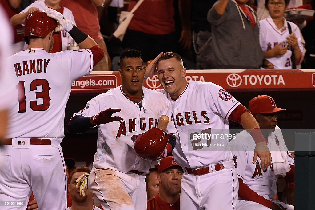 Jett Bandy #13 celebrates with teammates Yunel Escobar #6 and Mike Trout #27 of the Los Angeles Angels of Anaheim after hitting a solo homerun in the fifth inning against the Seattle Mariners at Angel Stadium of Anaheim on August 18, 2016 in Anaheim, California.