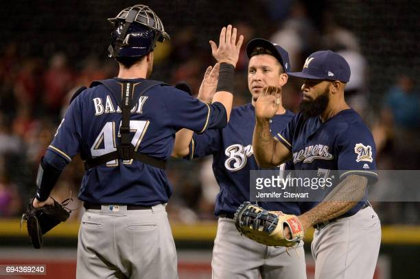 Jett Bandy Hernan Perez and Eric Thames of the Milwaukee Brewers celebrate after closing out the game against the Arizona Diamondbacks at Chase Field...