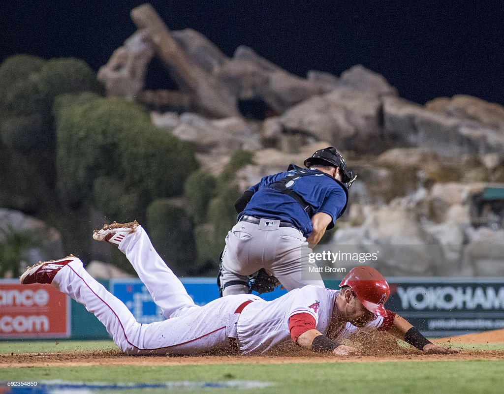 Jett Bandy of the Los Angeles Angels of Anaheim slides to score a goahead run on a RBI triple by Cliff Pennington as catcher Mike Zunino of the...