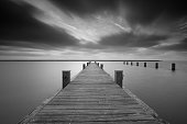 Jetty at lake Markermeer with a long exposure in black and white.
