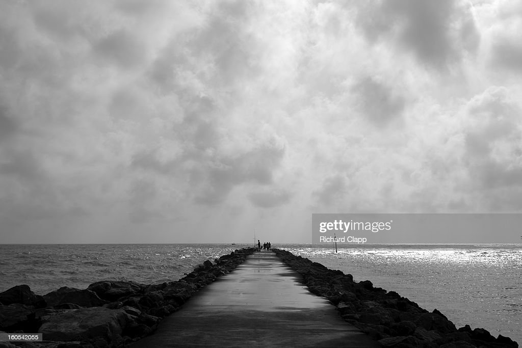 CONTENT] Jetty between the Gulf of Mexico and the Inland Coastal Waterway. Shows pier like structure receding into horizon on a stormy day, on the Gulf of Mexico.