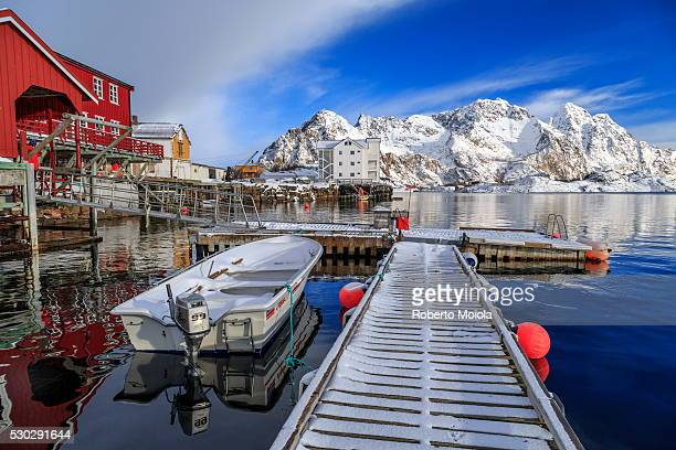 Jetty covered with snow after a night snowfall and boats docked in the harbor of Henningsvaer, Lofoten Islands, Arctic, Norway, Scandinavia, Europe