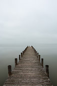 Deserted jetty, pier in foggy weather, vertical shot