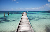 Wooden jetty perspective into the Indian Ocean seascape on a sunny day at Rottnest Island in Western Australia.