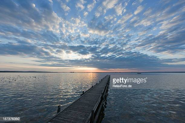 Jetty with magical cloudscape lakeside at sunset (XXL)
