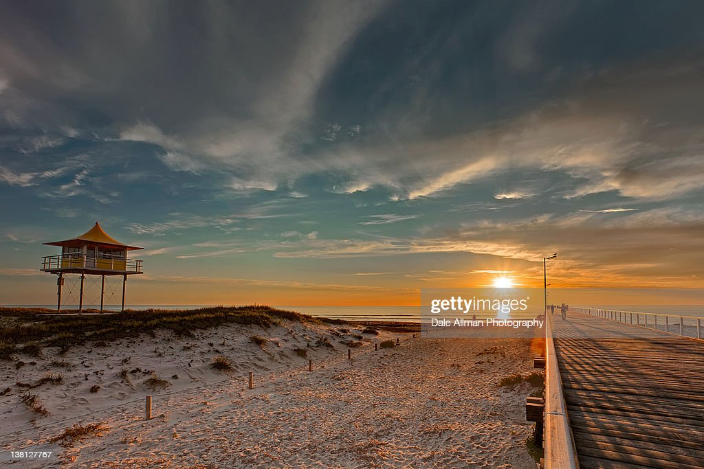 Jetty with surf lifesaving tower at sunset.