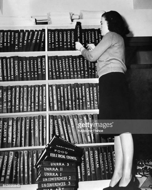 Jeune femme classant les différents livres contenant la conférence de l'ONU dans les archives du Service de la distribution de la Presse à New York...