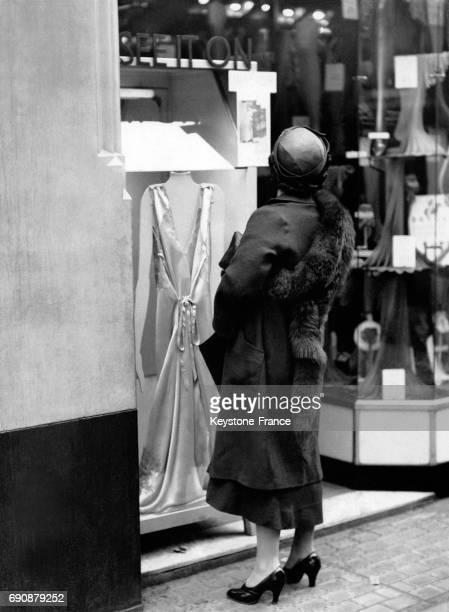 Jeune femme devant une cabine d'essayage installée dans la rue à Londres RoyaumeUni le 21 mai 1935