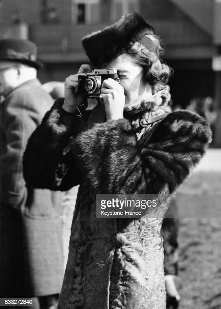 Jeune femme luxueusement habillée prenant une photo pendant une course hippique à Aintree RoyaumeUni le 24 mars 1939